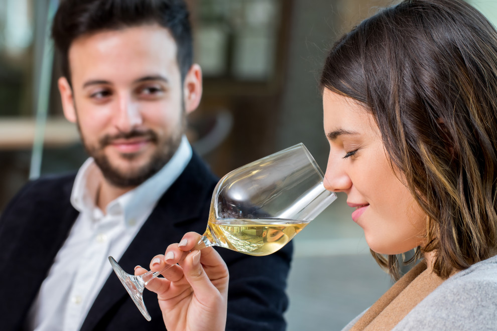 Close up portrait of young woman smelling white wine aroma at tasting.