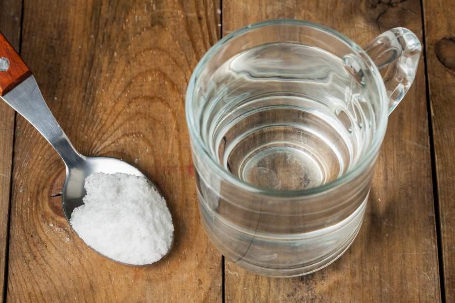 Verre d'eau avec dose de sucre dans cuillère